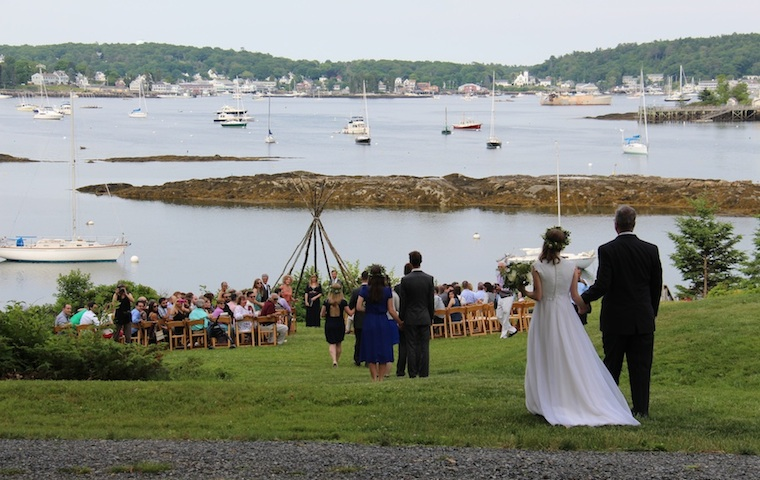 Father escorting his daughter down our waterfront lawn to meet here groom for a waterfront wedding overlooking Boothbay Harbor, Maine, at Harborfields On The Shore!